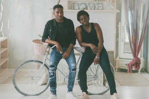 Deux amis heureux debout avec un vélo