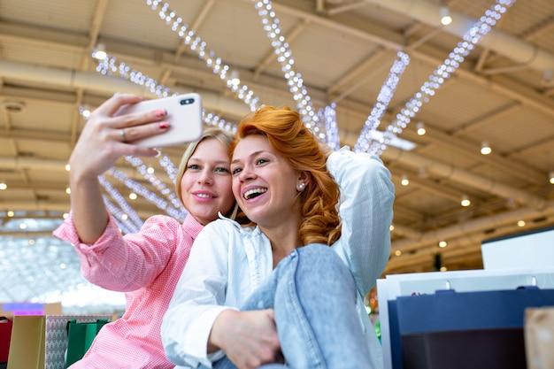 Deux amis heureux prennent selfie tout en faisant du shopping dans un centre commercial.