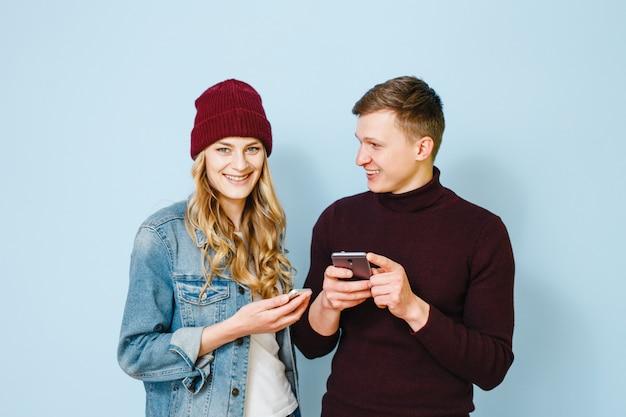 Deux amis heureux qui sont excités avec des téléphones dans leurs mains isolés sur fond bleu