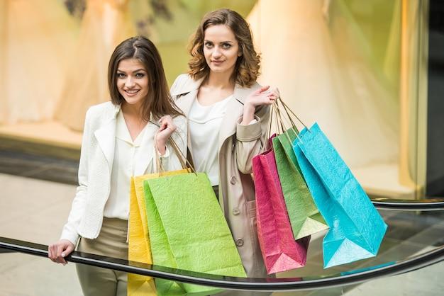 Deux amis heureux avec un sac à provisions font leurs courses dans un centre commercial.