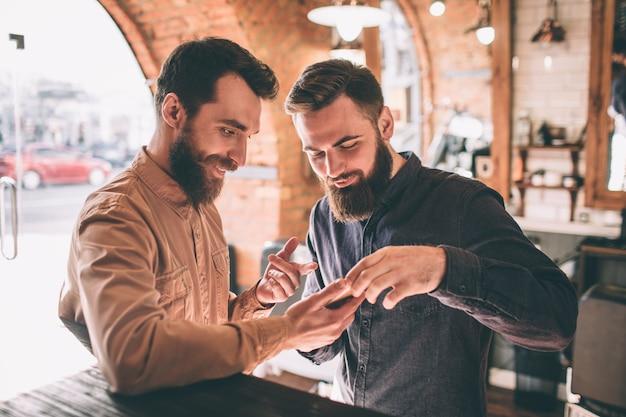Deux amis heureux sont dans un salon de coiffure. ils sont debout et regardent le téléphone. l'un d'eux montre quelque chose au téléphone à l'autre gars.