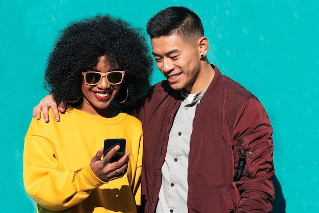 Deux amis heureux utilisant le mobile dans la rue. notion d'amitié.
