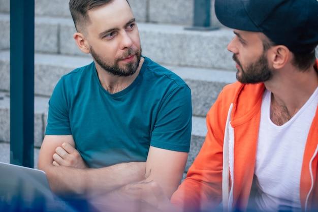 Deux amis hipster barbu heureux avec un ordinateur portable dans des vêtements décontractés sont assis sur les escaliers en plein air et ont une conversation.