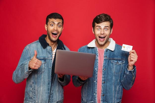 Deux amis hommes gais debout isolé sur mur rouge, tenant un ordinateur portable, montrant une carte de crédit en plastique