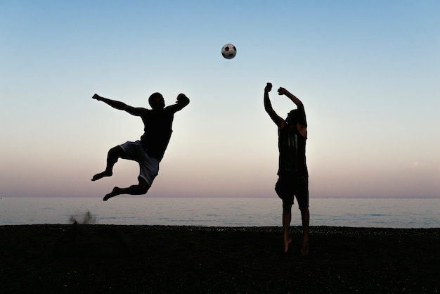 Deux amis jouant au football sur la plage.