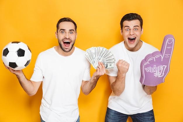 Deux amis joyeux et excités portant des t-shirts vierges isolés sur un mur jaune, applaudissant avec un gant en mousse et du football, montrant des billets en argent