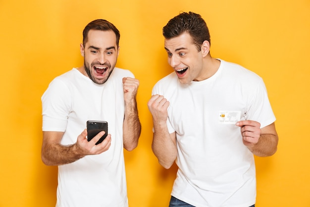 Deux amis joyeux et excités portant des t-shirts vierges isolés sur un mur jaune, regardant un téléphone portable, célébrant le succès