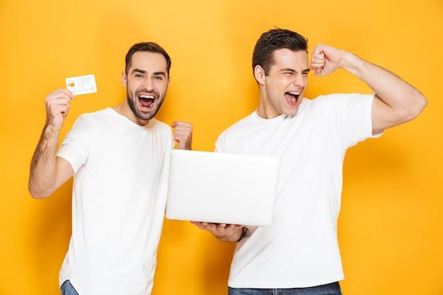 Deux amis joyeux et excités portant des t-shirts vierges isolés sur un mur jaune, utilisant un ordinateur portable, célébrant le succès, montrant une carte de crédit en plastique
