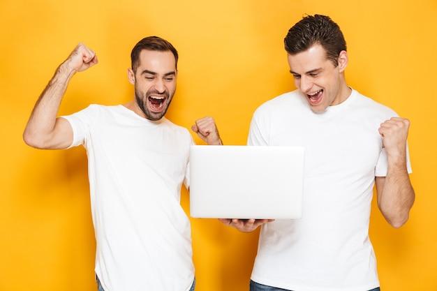 Deux amis joyeux et excités portant des t-shirts vierges isolés sur un mur jaune, utilisant un ordinateur portable, célébrant le succès