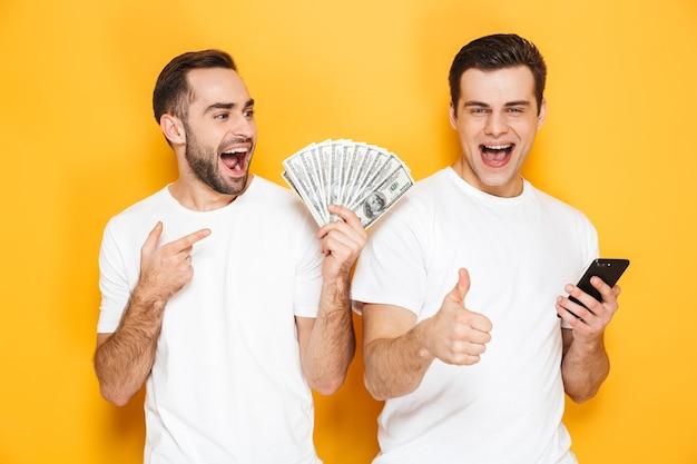 Deux amis joyeux et excités portant des t-shirts vierges isolés sur un mur jaune, utilisant un téléphone portable, montrant des billets en argent