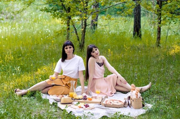 Deux amis joyeux jeunes filles ayant un pique-nique