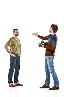Les deux amis masculins avec appareil photo sur blanc