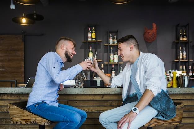 Deux amis masculins assis au bar contre verres de boissons
