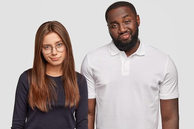 Deux amis multiethniques plissent les yeux et froncent les sourcils, ont déplu aux expressions faciales