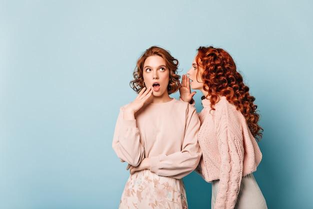 Deux amis partageant des potins. photo de studio de filles parlant sur fond bleu.