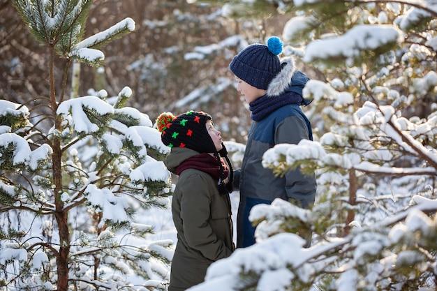 Deux amis de petit garçon s'embrassent dans une journée d'hiver neigeuse. frère amour. concept d'amitié.