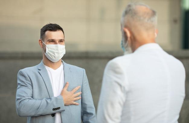 Deux amis portant des masques pour se rencontrer et se tenir debout à l'extérieur