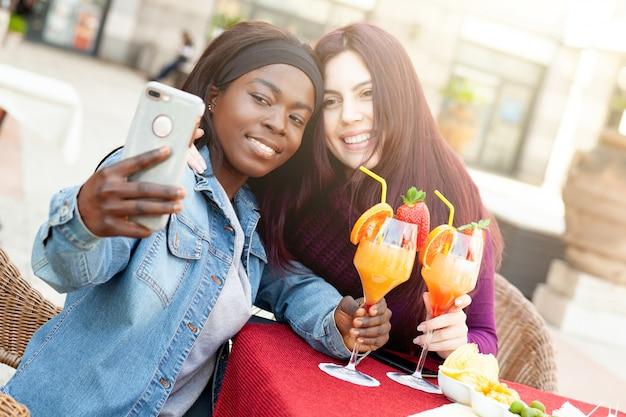 Deux amis prenant un selfie tout en acclamant avec des cocktails.