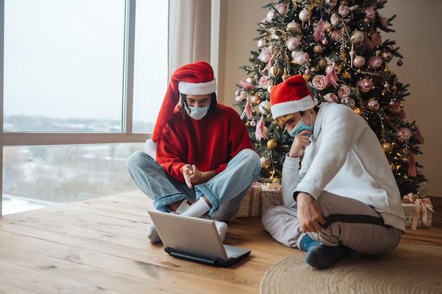Deux amis près de l'ordinateur portable interagissent via des appels vidéo