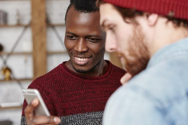 Deux amis de races différentes s'amusant à l'intérieur, en utilisant un gadget électronique