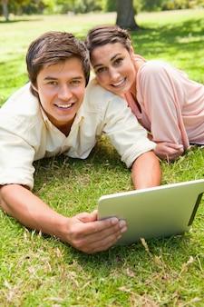 Deux amis regardant vers l'avenir car ils utilisent une tablette ensemble