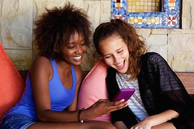 Deux amis en riant et en regardant le téléphone mobile