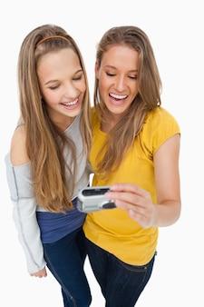 Deux amis rient en vérifiant leur photo sur un appareil photo numérique