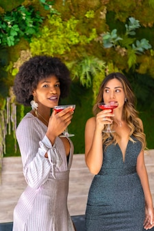 Deux amis en robes de gala ayant un cocktail lors d'une fête dans un hôtel, style de vie. style de vie glamour, fête exclusive