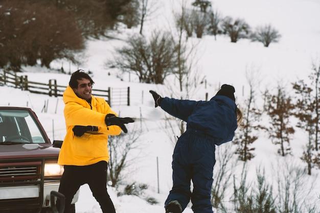 Deux amis se battre avec des boules de neige dans la neige avec la voiture 4 roues motrices sur l'arrière-plan