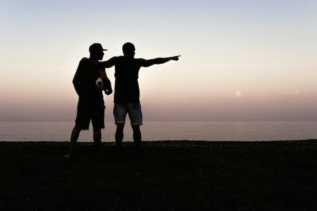 Deux amis se détendent après avoir joué au football sur la plage.