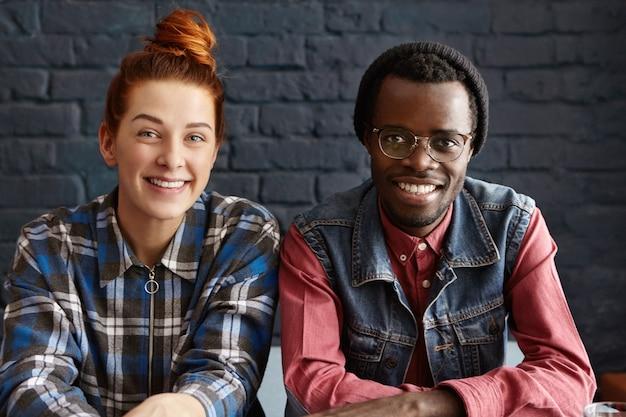 Deux amis se détendre au café, assis à table près l'un de l'autre contre le mur de briques noires