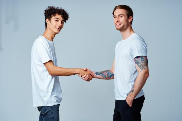 Deux amis se tiennent la main dans un mur isolé de t-shirts blancs