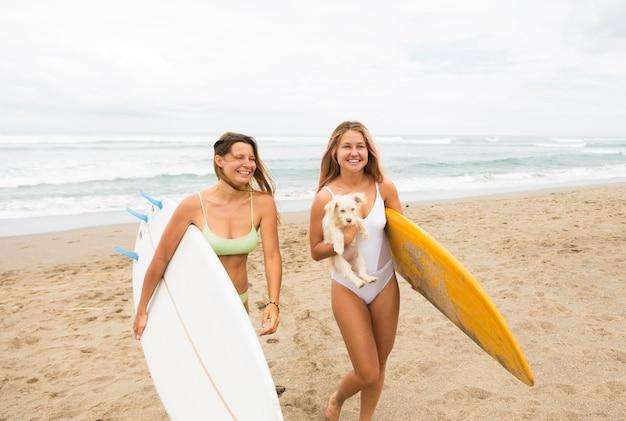 Deux amis smiley à la plage avec des planches de surf