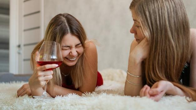 Deux amis sont allongés sur le canapé et discutent. belle blonde tenant un verre de vin rouge dans sa main