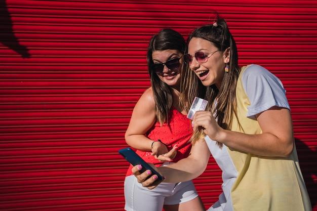 Deux amis souriants parlant et montrant une carte de crédit lors d'un appel vidéo en ligne.