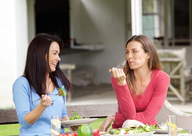 Deux amis souriants en train de déjeuner