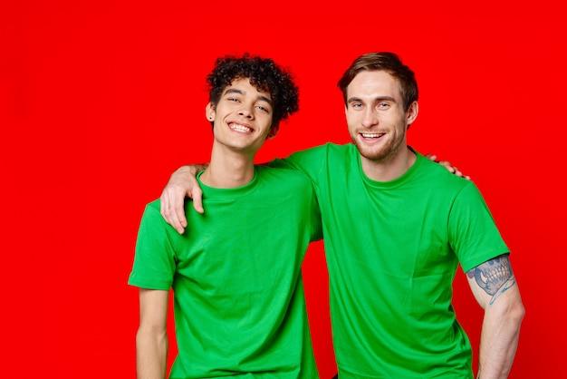 Deux amis en t-shirts verts étreignent fond rouge amusant
