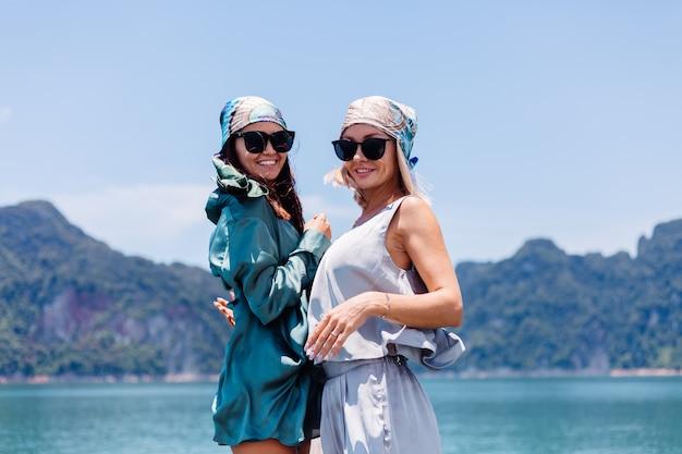 Deux amis touristiques blogueuse femme heureuse en costume de soie et écharpe et lunettes de soleil en vacances voyagent en thaïlande sur un bateau asiatique, le parc national de khao sok.