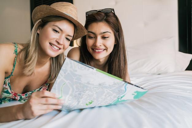 Deux amis voyageurs organisent leur voyage dans une chambre d'hôtel.