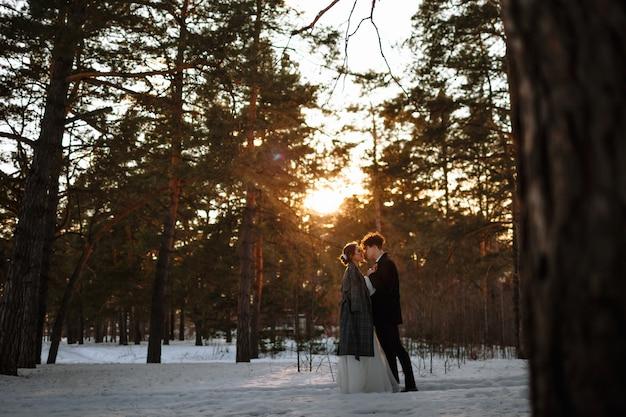 Deux amoureux debout dans une forêt d'hiver sur fond de coucher de soleil. séance photo de mariage