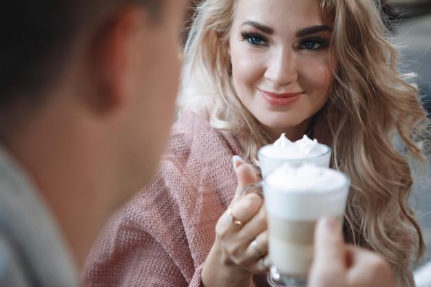 Deux amoureux, un homme et une femme à une table dans un café. câlin, caresse, bois du latte. heureux couple traditionnel, bonheur familial.