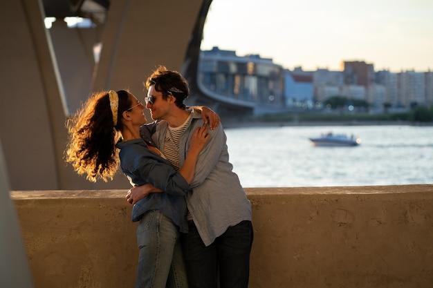 Deux amoureux s'embrassent au coucher du soleil, un couple élégant et heureux embrasse un beau jeune homme et une femme s'embrassant au soleil