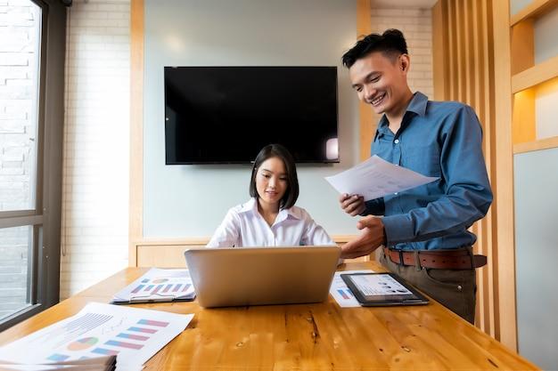 Deux analystes discutent des données en ligne devant un ordinateur portable.
