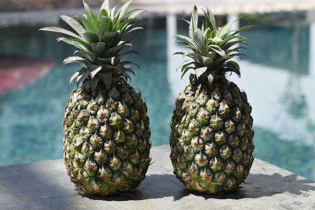 Deux ananas mûrs au bord de la piscine