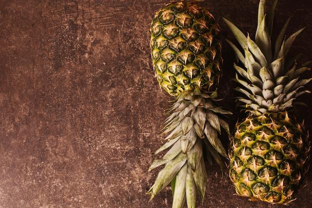 Deux ananas mûrs gisant sur une table en marbre foncé. délicieux fruits. alimentation équilibrée.
