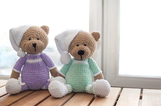 Deux animaux en peluche brun ours en peluche sur table en bois.