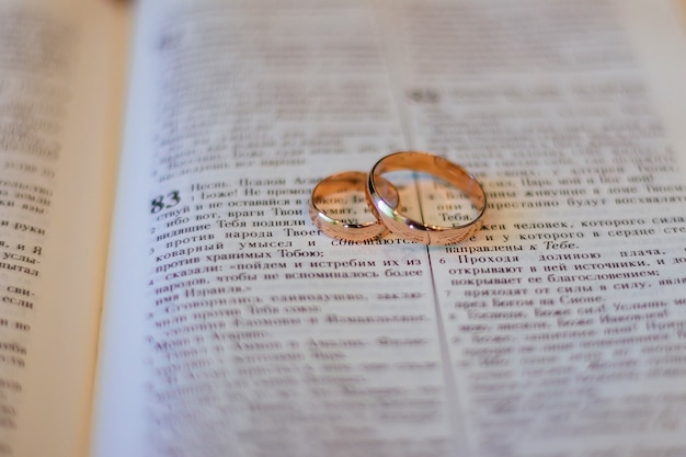 Deux anneaux de mariage sur des anneaux de mariage de bible de bible