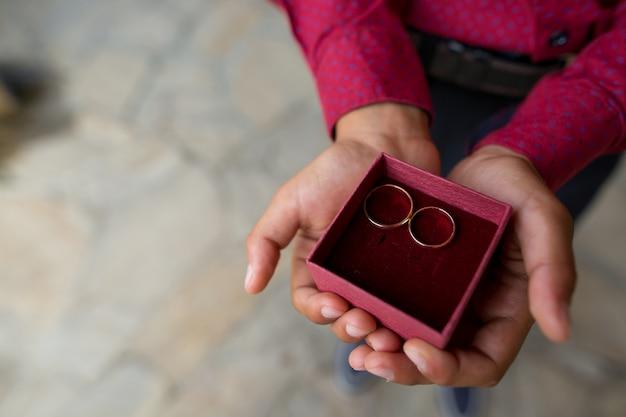 Deux anneaux de mariage entre les mains d'un porteur de bague