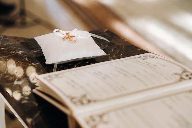 Deux anneaux de mariage en or reposent sur un coussin dans la salle de mariage.