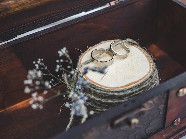 Deux anneaux de mariage se trouvant sur un fond de fleurs